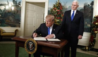 Vice President Mike Pence looks on as President Donald Trump signs a proclamation to officially recognize Jerusalem as the capital of Israel, in the Diplomatic Reception Room of the White House, Wednesday, Dec. 6, 2017, in Washington. (AP Photo/Evan Vucci)