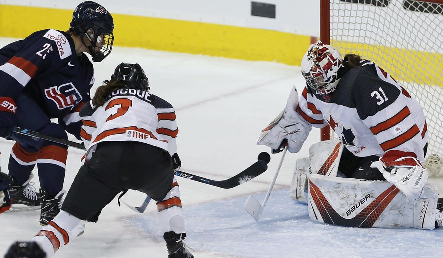 Canada goalie Genevieve Lacasse (31) saves the shot by the United States' Alex Carpenter (25) as Canada's Jocelyne Larocque (3) defends during the first period of a hockey game Tuesday, Dec. 5, 2017, in Winnipeg, Manitoba. (John Woods/The Canadian Press via AP)