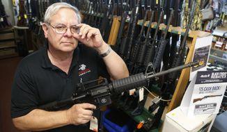 In this Tuesday, Dec. 5, 2017 photo, manager of Bob Moates Sports Shop, David Hancock, poses with a firearm in the shop in Richmond, Va. Hancock says he is not expecting any major changes in the states gun laws as a result of the election of many Democrats in the Virginia House of Delegates. (AP Photo/Steve Helber)