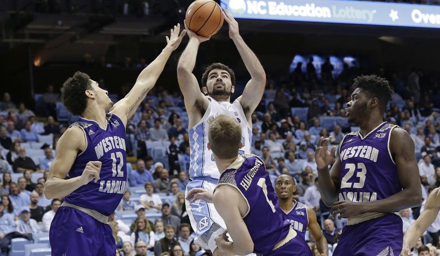 North Carolina's Luke Maye shoots while Western Carolina's Marc Gosselin (12), Matt Halvorsen (2) and Mike Amius (23) defend during the first half of an NCAA college basketball game in Chapel Hill, N.C., Wednesday, Dec. 6, 2017. (AP Photo/Gerry Broome)
