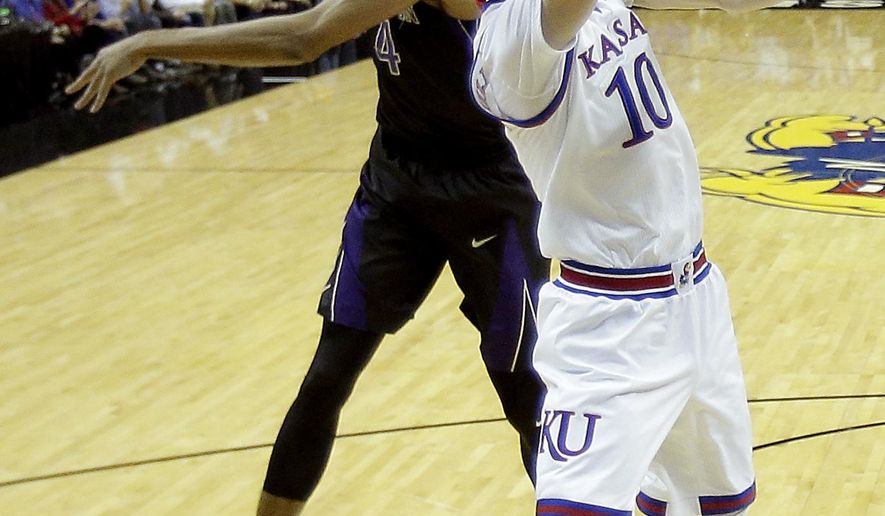 Kansas' Sviatoslav Mykhailiuk (10) shoots in front ofWashington's Matisse Thybulle (4) during the first half of an NCAA college basketball game Wednesday, Dec. 6, 2017, in Kansas City, Mo. (AP Photo/Charlie Riedel)