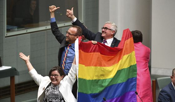 Members of parliament, from left, Cathy McGowan, Adam Brandt and Andrew Wilkie celebrate the passing of the Marriage Amendment Bill in the House of Representatives at Parliament House in Canberra, Thursday, Dec. 7, 2017. Gay marriage was endorsed by 62 percent of Australian voters who responded to a government-commissioned postal ballot by last month. (Mick Tsikas/AAP Image via AP)