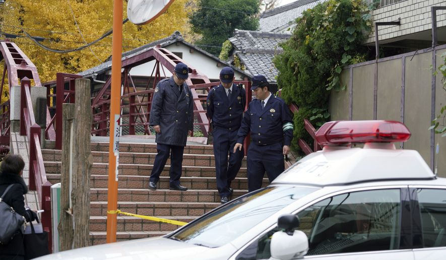 Police officers walk near the scene of a stabbing incident at Tomioka Hachimangu shrine in Tokyo Friday, Dec. 8, 2017. Police say three people have died in the stabbing attack on Thursday night at the prominent shrine, including the head priest and the attacker, who apparently took his own life. (AP Photo/Eugene Hoshiko)