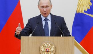 Russian President Vladimir Putin gestures while speaking to employees of Rostec Corporation during an awarding ceremony at the Novo-Ogaryovo state residence outside in Moscow, Russia, Thursday, Dec. 7, 2017. The spokesman for Vladimir Putin says the Russian president has not decided yet whether to run for office next year as an independent candidate or secure support from the ruling party. (Sergei Karpukhin/Pool Photo via AP)