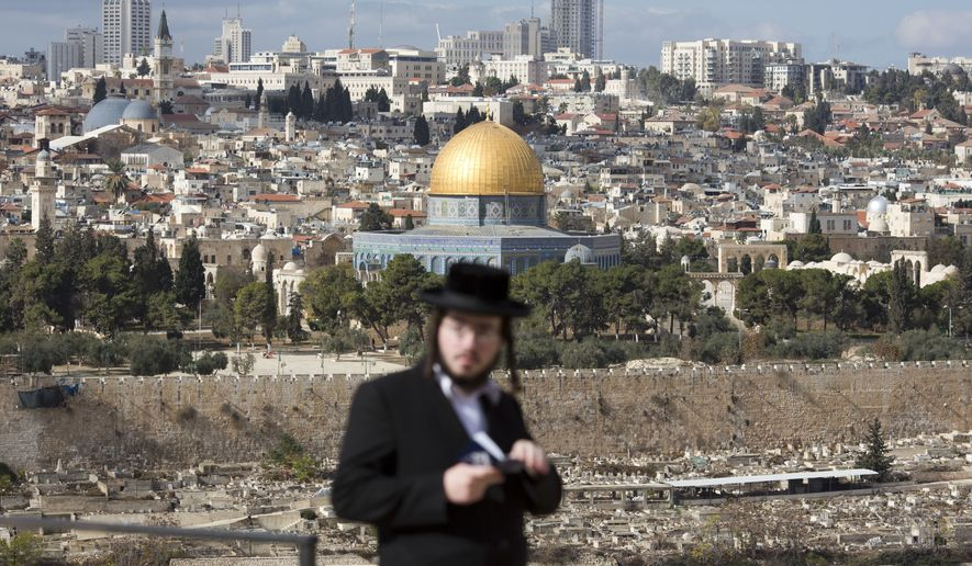 The Dome of the Rock Mosque in the Al Aqsa Mosque compound in Jerusalem's Old City is seen while a Jewish orthodox man reads from a holy book in a cemetery in Jerusalem, Thursday, Dec. 7, 2017, a day after U.S. President Donald Trump's recognition of Jerusalem as Israel's capital. (AP Photo/Ariel Schalit)