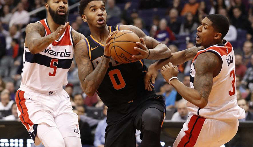 Phoenix Suns forward Marquese Chriss (0) drives between Washington Wizards forward Markieff Morris (5) and guard Bradley Beal (3) during the second half of an NBA basketball game, Thursday, Dec. 7, 2017, in Phoenix. (AP Photo/Matt York)