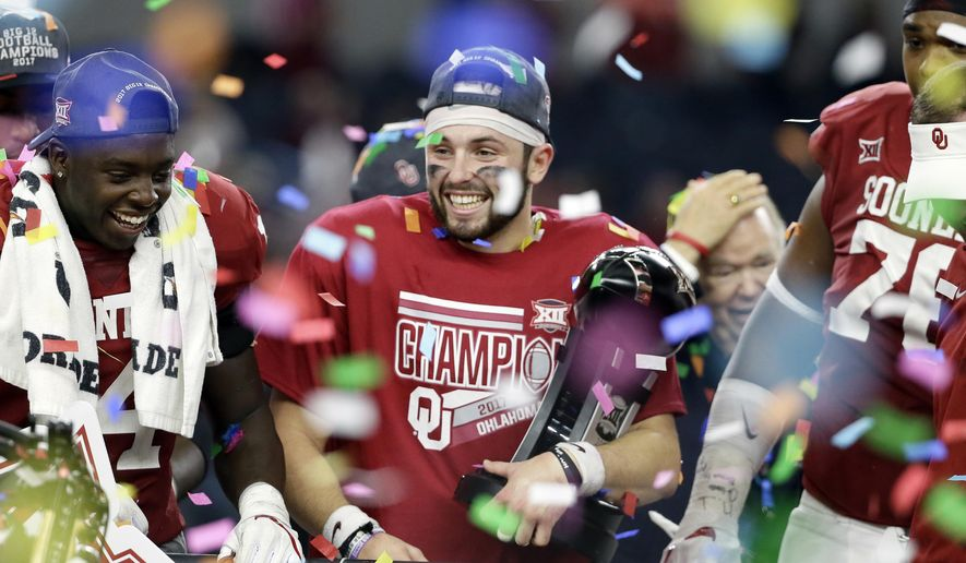 FILE - In this Dec. 2, 2017, file photo, Oklahoma quarterback Baker Mayfield, center, holds his Most Outstanding Player trophy as he celebrates with the team after their 41-17 win in the the Big 12 Conference championship NCAA college football game against TCU, in Arlington, Texas. Baker Mayfield is the AP player of the year, becoming the fourth Oklahoma quarterback to win the award since it was established in 1998. (AP Photo/Tony Gutierrez, File)