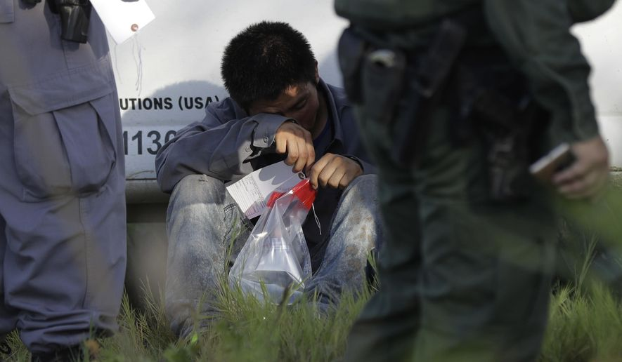 In this Aug. 11, 2017, photo, an immigrant suspected of crossing into the United States illegally along the Rio Grande near Granjeno, Texas, is held by U.S. Customs and Border Patrol agents. The election of President Donald Trump contributed to a dramatic downturn in migration, causing the number of arrests at the border to hit an all-time low in April. But since then, the number of immigrants caught at the southern border has been increasing monthly. (AP Photo/Eric Gay)