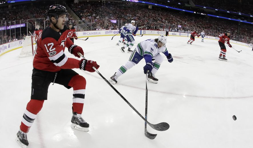 New Jersey Devils defenseman Ben Lovejoy (12) clears the puck as Vancouver Canucks left wing Loui Eriksson (21), of Sweden, tries to get his stick on it during the first period of an NHL hockey game, Friday, Nov. 24, 2017, in Newark, N.J. (AP Photo/Julio Cortez)