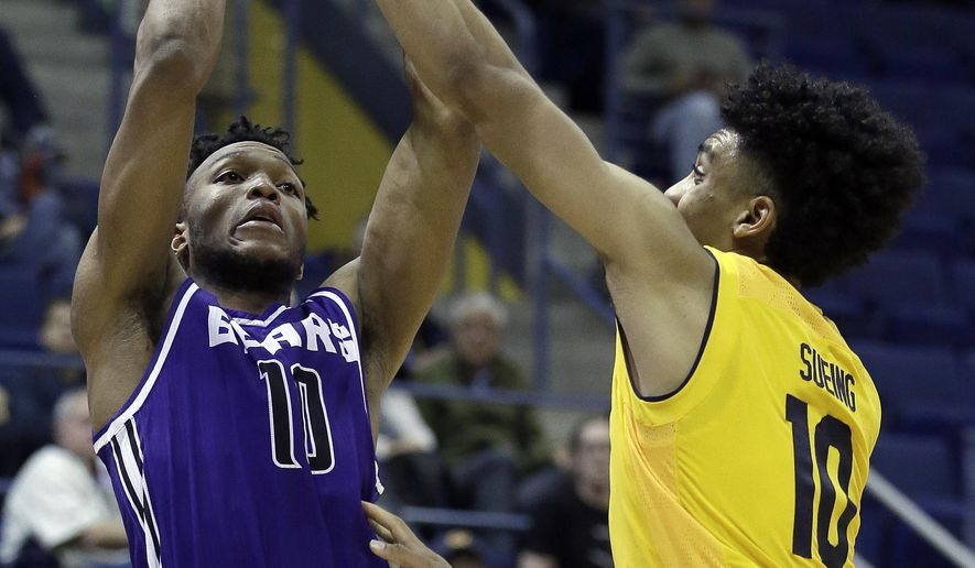 Central Arkansas guard Mathieu Kamba, left, shoots against California's Justice Sueing during the second half of an NCAA college basketball game Wednesday, Dec. 6, 2017, in Berkeley, Calif. (AP Photo/Ben Margot)
