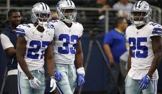 FILE - In this Oct. 8, 2017, file photo, Dallas Cowboys' Jourdan Lewis (27), Chidobe Awuzie (33) and Xavier Woods (25) warm up before an NFL football game against the Green Bay Packers in Arlington, Texas. Awuzie is finally healthy, which means the Cowboys are finally getting a look at a trio of rookie defensive backs together after a significant investment in the draft that included fellow cornerback Jourdan Lewis and safety Xavier Woods. (AP Photo/Ron Jenkins, File)