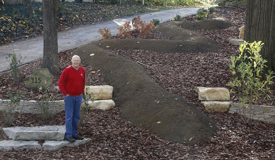 In a Nov. 9, 2017 photo, inspired by Norse mythology and the Ohio serpent mound,  Donn Young of Clintonville, built his own serpent mound in his yard. [Tom Dodge/The Columbus Dispatch via AP)