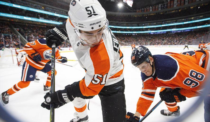 Philadelphia Flyers' Valtteri Filppula (51) battles for the puck with Edmonton Oilers' Jesse Puljujarvi (98) during the second period of an NHL hockey game Wednesday, Dec. 6, 2017, in Edmonton, Alberta. (Jason Franson/The Canadian Press via AP)