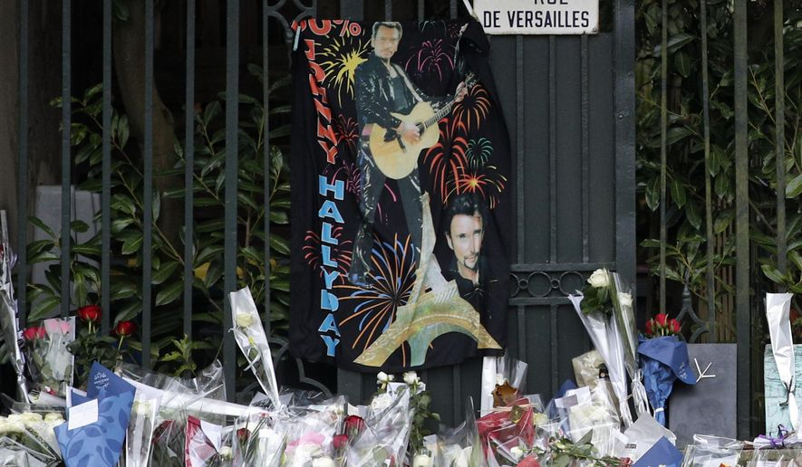 Flowers brought by fans lay outside Johnny Hallyday's house in Marnes-la-Coquette, outside Paris, Thursday, Dec.7, 2017. Johnny Hallyday, France's biggest rock star for more than half a century and an icon who packed sports stadiums and all but lit up the Eiffel Tower with his pumping pelvis and high-voltage tunes, has died. He was 74. (AP Photo/Christophe Ena)