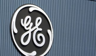 This June 24, 2014, file photo, shows the General Electric logo at a plant in Belfort, France. On Thursday, Dec. 7, 2017, GE said it will cut 12,000 jobs in its power division as alternative energy supplants demand for coal and other fossil fuels. (AP Photo/Thibault Camus, File)