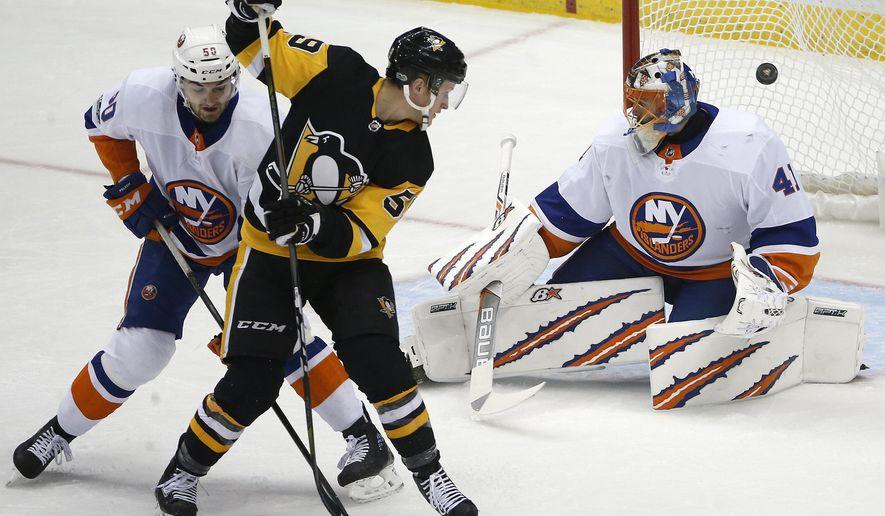 Pittsburgh Penguins' Jake Guentzel (59) redirects a shot by Kris Letang past New York Islanders goalie Jaroslav Halak (41), with Adam Pelech (50) defending during the first period of an NHL hockey game in Pittsburgh, Thursday, Dec. 7, 2017. (AP Photo/Gene J. Puskar)