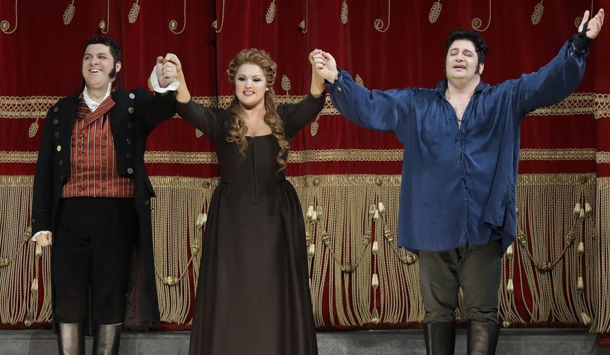 """Russian soprano Anna Netrebko, center, Azerbaijani tenor Yusif Eyvazov, right, and Italian baritone Luca Salsi acknowledge the applause of the audience at the end of La Scala opera house's gala season opener, Umberto Giordano's opera """"Andrea Chernier"""", at the Milan La Scala theater, Italy, Thursday, Dec. 7, 2017. The season-opener Thursday, held each year on the Milan feast day St. Ambrose, is considered one of the highlights of the European cultural calendar. (AP Photo/Luca Bruno)"""