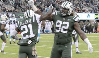 "FILE - In this Nov. 26, 2017, file photo, New York Jets defensive end Leonard Williams (92) and cornerback Morris Claiborne (21) celebrate during the second half of the team's NFL football game against the Carolina Panthers in East Rutherford, N.J. Williams has just two sacks this season, but he has a whopping 26 quarterback hits. That means he's getting quarterbacks off their spots, forcing throws and making them downright uncomfortable.  ""People want to see the sacks,"" Williams acknowledged Thursday, Dec. 7. ""I wouldn't really call a QB hit a stat or anything. I just think of it as being disruptive. That's what a defensive player wants to do, is be disruptive in any way possible. ""No matter what type of stat it is, if you're being disruptive, that's a good defensive play."" (AP Photo/Bill Kostroun, File)"