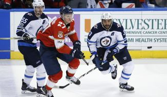 Florida Panthers center Nick Bjugstad (27) and Winnipeg Jets defenseman Dustin Byfuglien (33) and center Mark Scheifele (55) compete for the puck during the second period of an NHL hockey game Thursday, Dec. 7, 2017, in Sunrise, Fla. (AP Photo/Wilfredo Lee)