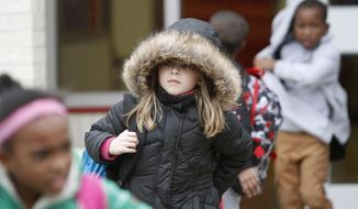 North Bay Elementary School student Vivian Moore, 7, of Biloxi, Miss., braces against the cold weather as she walks to her bus after school on Wednesday, Dec., 6, 2017. Forecasters say conditions could be right for snowfall in South Mississippi late Thursday or early Friday. (John Fitzhugh/The Sun Herald via AP)