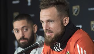 Seattle Sounders goaltender Stefan Frei answers a question as  forward Clint Dempsey listens during a news conference in Toronto, Thursday Dec. 7, 2017. The Sounders face Toronto FC on Saturday in the MLS Cup soccer final. (Frank Gunn/The Canadian Press via AP)