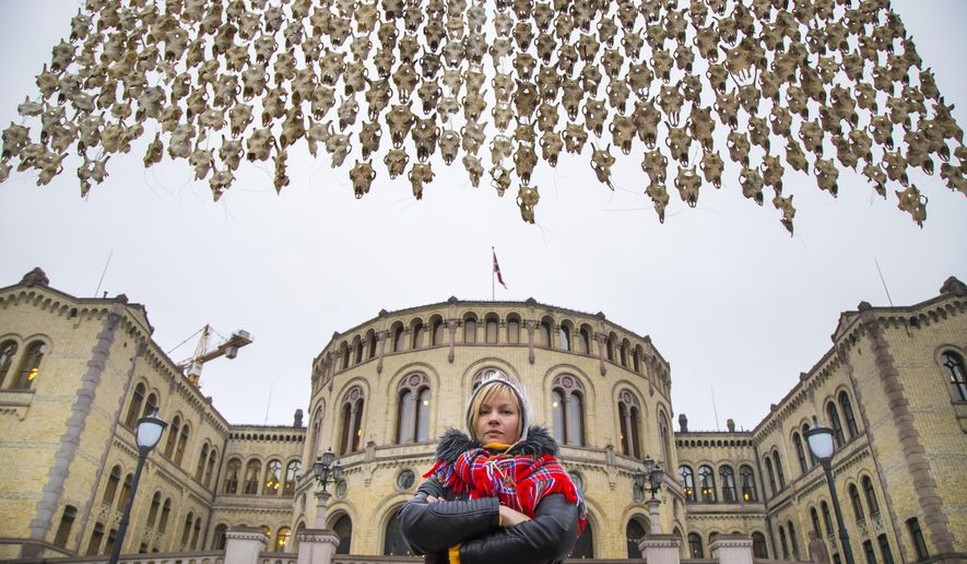 Sami artist Maret Anne Sara stands near her art piece of 400 reindeer skulls hanging in front of the Parliament building in Oslo, Norway, Wednesday Dec. 6, 2017. (Heiko Junge/NTB Scanpix via AP)