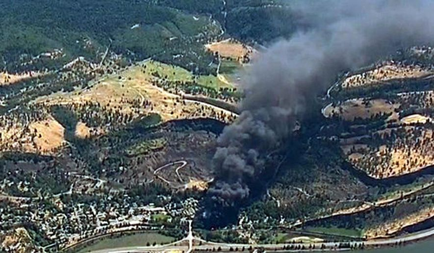 FILE- In this June 3, 2016, file image, from video provided by KGW-TV, smoke billows from a Union Pacific train that derailed near Mosier, Ore., in the scenic Columbia River Gorge. The Trump administration is angering environmental groups and residents of the Columbia River Gorge by rolling back a 2015 rule on oil train safety. (KGW-TV via AP, File)