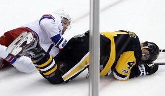 Pittsburgh Penguins' Justin Schultz (4) lies on the ice after a collision with New York Rangers' Rick Nash, left, during the first period of an NHL hockey game in Pittsburgh, Tuesday, Dec. 5, 2017. Schultz left the game with a lower body injury and returned briefly in the second period and did not play in the third. The Rangers won 4-3. (AP Photo/Gene J. Puskar)