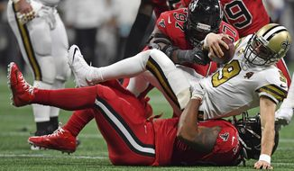 Atlanta Falcons defensive tackle Dontari Poe, bottom, and Atlanta Falcons defensive tackle Grady Jarrett (97) sack New Orleans Saints quarterback Drew Brees (9) during the second half of an NFL football game, Thursday, Dec. 7, 2017, in Atlanta. (AP Photo/Danny Karnik)