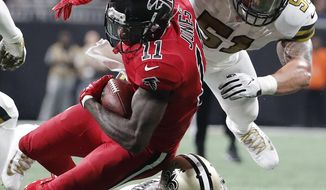 Atlanta Falcons wide receiver Julio Jones (11) is hit by New Orleans Saints cornerback Marshon Lattimore (23) and New Orleans Saints middle linebacker Manti Te'o (51) during the second half of an NFL football game, Thursday, Dec. 7, 2017, in Atlanta. (AP Photo/David Goldman)
