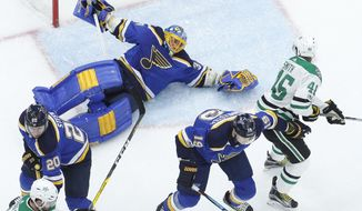 St. Louis Blues goalie Jake Allen, top left, falls while reaching for a puck as Dallas Stars' Gemel Smith (46) watches during the first period of an NHL hockey game Thursday, Dec. 7, 2017, in St. Louis. (AP Photo/Jeff Roberson)