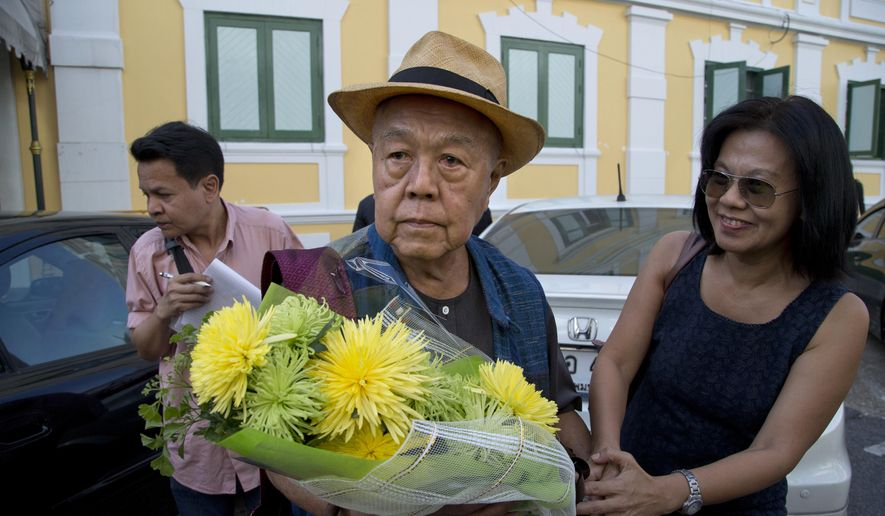 Sulak Sivaraksa, center receives flowers from a well-wisher outside a military court Thursday, Dec. 7, 2017 in Bangkok, Thailand as he walks in to find out whether military prosecutor has proceeded with the indictment against him on lese majeste.   A Thai military court has delayed a decision on whether to prosecute the prominent historian and social critic who suggested that a famed duel on elephant-back won by a Thai king against a Burmese prince 500 years ago may not actually have happened. (AP Photo/Gemunu Amarasinghe)