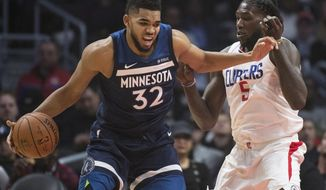 Minnesota Timberwolves center Karl-Anthony Towns, left, tries to drive past Los Angeles Clippers forward Montrezl Harrell during the first half of an NBA basketball game on Wednesday, Dec. 6, 2017, in Los Angeles. (AP Photo/Kyusung Gong)