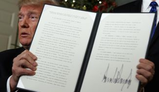 President Donald Trump holds up a proclamation to officially recognize Jerusalem as the capital of Israel, in the Diplomatic Reception Room of the White House, Wednesday, Dec. 6, 2017, in Washington. (AP Photo/Evan Vucci)