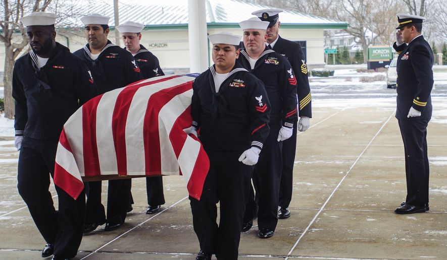 Members of the Navy Operation Support Center from Battle Creek, Mich., carry the casket of Navy Airman Albert Rybarczyk into Starks Family Funeral Home, Thursday, Dec. 7, 2017, in St. Joseph, Mich. The 22-year-old Rybarczyk was killed when his plane crashed during World War II. The wreckage was discovered in 2014 and DNA samples of the remains were taken and a positive identification was confirmed in August. (Kaytie Boomer/The Grand Rapids Press via AP)