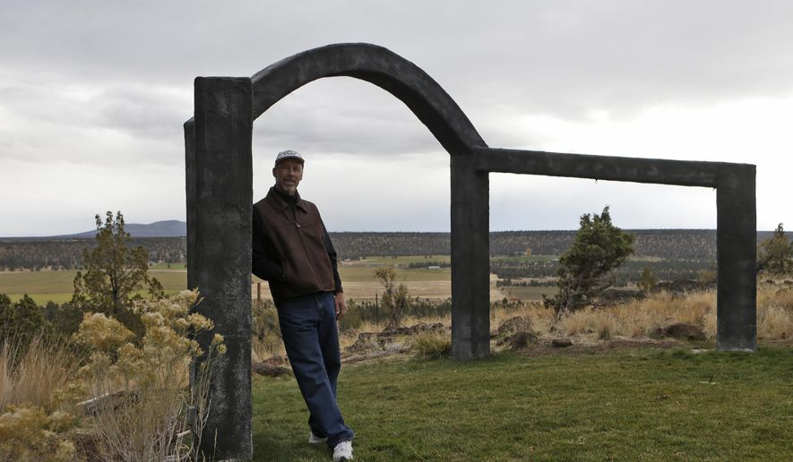 In this Oct. 19, 2017 photo, John Shepherd, a pastor at his home church and officiant during the wedding ceremonies he hosts, poses against the archway he built for hosting wedding ceremonies at his venue, Shepherdsfield, outside Sisters, Ore. Deschutes County is wading into a long-running zoning debate that pits mule deer against churches. The issue came to a head three years ago when the county told a Shepherd he was in violation for hosting a church at his home and conducting outdoor weddings within the zoned area.  (Joe Kline/The Bulletin via AP)
