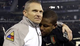 FILE - In this Dec. 13, 2014, file photo, Army head coach Jeff Monken, left, embraces running back Larry Dixon after losing 17-10 to Navy in an NCAA college football game, in Baltimore. Monkens second season at Army in 2015 ended with 10 losses and a record 14th straight defeat to Navy. While it pointed to more of the same for a struggling program, Monken was confident a West Point turnaround was imminent thanks to successful recruiting and the number of close losses. Monken was proven right.  (AP Photo/Patrick Semansky, File)