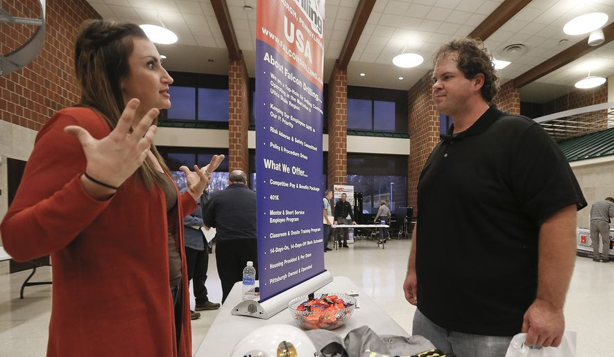 In this Thursday, Nov. 2, 2017, file photo, a recruiter from a driller in the shale gas industry, left, speaks with an attendee at a job fair in Cheswick, Pa. (AP Photo/Keith Srakocic) ** FILE **