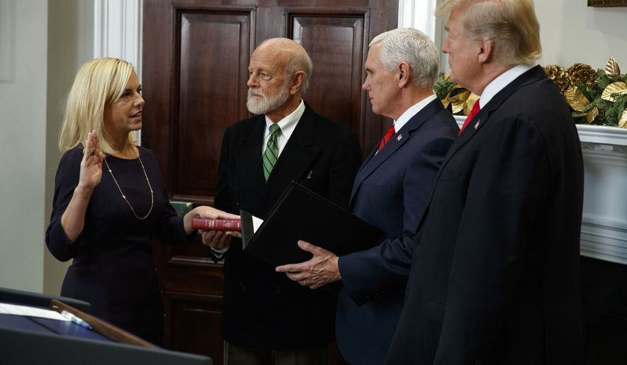 President Donald Trump, right, watches as Kirstjen Nielsen is sworn in as the new Secretary of Homeland Security by Vice President Mike Pence, in the Roosevelt Room of the White House, Friday, Dec. 8, 2017, in Washington. (AP Photo/Evan Vucci)