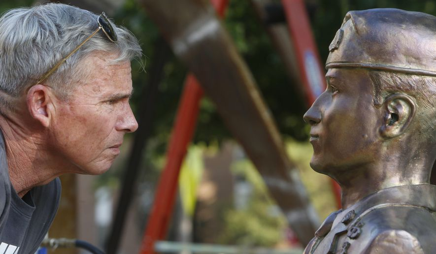 FILE- In this Nov. 3, 2017 file photo, sculptor, Tuscaloosa resident and retired Marine Col. Lee Busby checks the image of Mark Forester he sculpted outside the University of Alabama Foundry in Tuscaloosa, Ala. Write-in votes could matter in Alabama's Senate race between Republican Roy Moore and Democrat Doug Jones. Sculptor Lee Busby is running as a write-in with several others. (Gary Cosby Jr. /The Tuscaloosa News via AP)