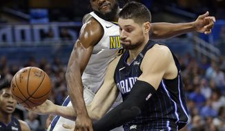 Denver Nuggets' Kenneth Faried, left, knocks the ball out of the hands of Orlando Magic's Nikola Vucevic as they battle for a rebound during the first half of an NBA basketball game, Friday, Dec. 8, 2017, in Orlando, Fla. (AP Photo/John Raoux)