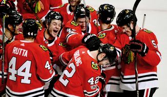 Chicago Blackhawks defenseman Gustav Forsling, (42) celebrates with teammates after Forsling scored against the Buffalo Sabres during overtime in an NHL hockey game Friday Dec. 8, 2017, in Chicago. The Blackhawks won 3-2. (AP Photo/Matt Marton)