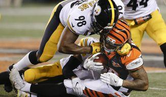 Cincinnati Bengals running back Joe Mixon, bottom, is tackled by Pittsburgh Steelers inside linebacker Vince Williams (98) in the first half of an NFL football game, Monday, Dec. 4, 2017, in Cincinnati. (AP Photo/Gary Landers)