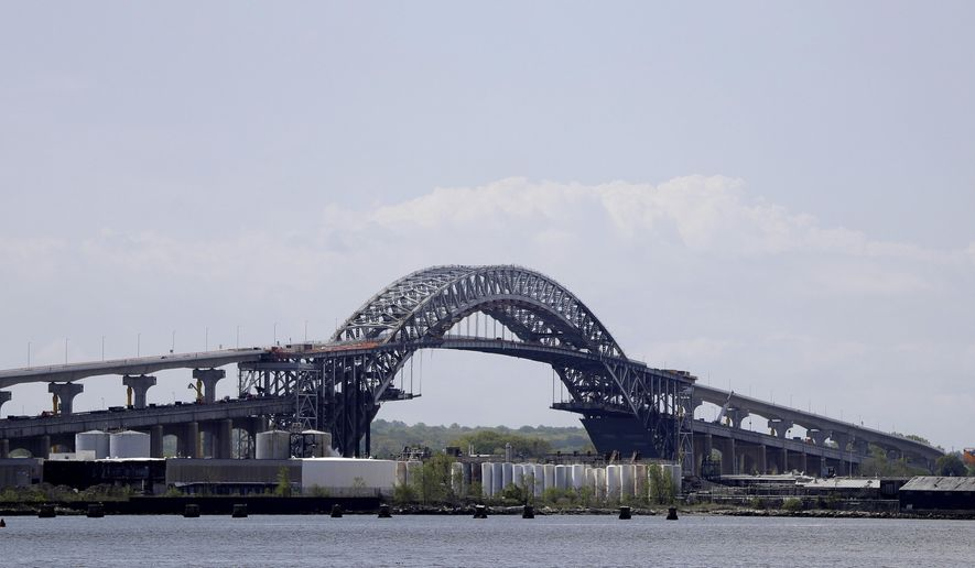 File- This  May 2, 2017, file photo shows the Bayonne Bridge prior to a news conference announcing the bridge project completion, seen from Elizabeth, N.J. The elevation of the Bayonne Bridge was projected to cost about $1.3 billion before construction began more than four years ago.  This week, the Port Authority of New York and New Jersey, which owns and operates the bridge, approved allocating between $350 million and $400 million more, an overrun of more than 25 percent. (AP Photo/Julio Cortez, File)