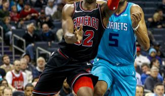 Chicago Bulls guard Kris Dunn, left, drives to the basket past Charlotte Hornets guard Nicolas Batum in the second half of an NBA basketball game in Charlotte, N.C., Friday, Dec. 8, 2017. Chicago won 119-111. (AP Photo/Nell Redmond)