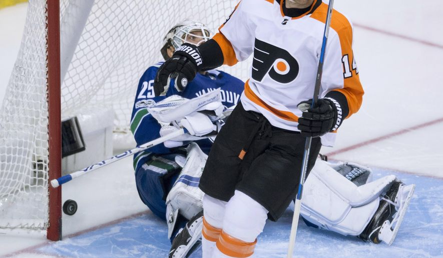 Philadelphia Flyers center Sean Couturier (14) celebrates his goal against Vancouver Canucks goalie Jacob Markstrom (25) during the second period of an NHL hockey game Thursday, Dec. 7, 2017, in Vancouver, British Columbia. (Jonathan Hayward/The Canadian Press via AP)