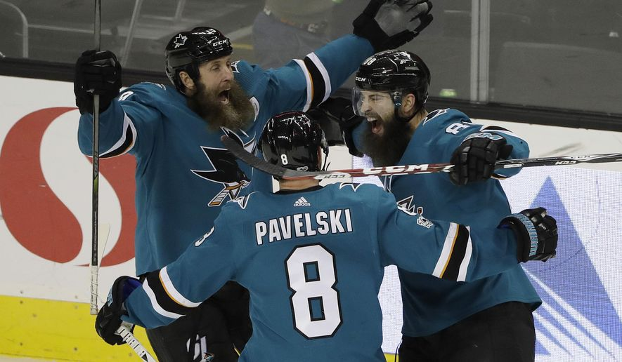 San Jose Sharks defenseman Brent Burns, right, celebrates his game-winning goal with teammates Joe Thornton, left, and Joe Pavelski (8) during overtime of an NHL hockey game against the Carolina Hurricanes on Thursday, Dec. 7, 2017, in San Jose, Calif. San Jose won 5-4. (AP Photo/Marcio Jose Sanchez)