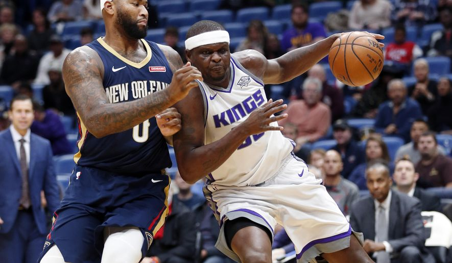 Sacramento Kings forward Zach Randolph, right, drives to the basket against New Orleans Pelicans center DeMarcus Cousins (0) during the first half of an NBA basketball game in New Orleans, Friday, Dec. 8, 2017. (AP Photo/Gerald Herbert)