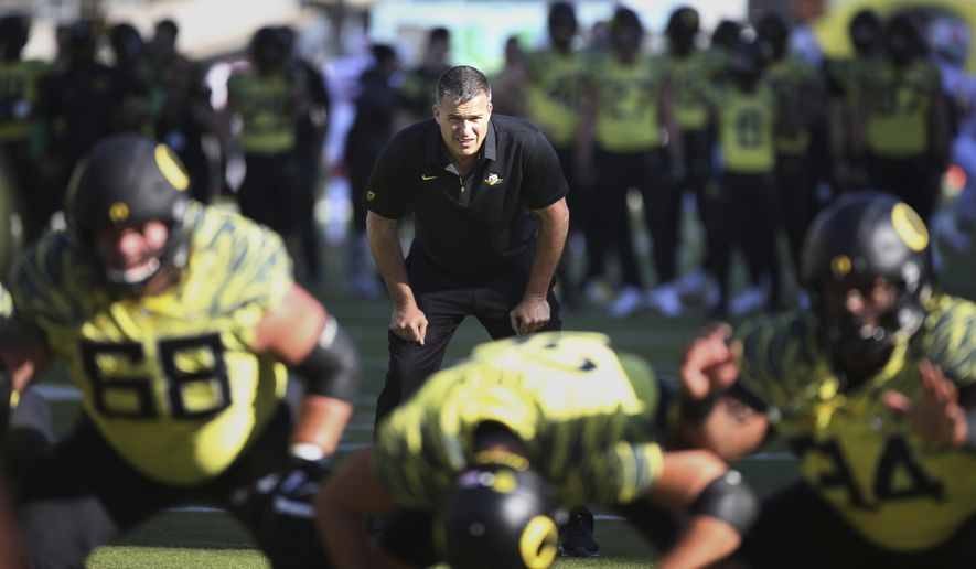 FILE - In this Oct. 28, 2017, file photo, Oregon co-offensive coordinator Mario Cristobal watches a special team warmup drill before an NCAA college football game against Utah, in Eugene, Ore. A person with direct knowledge of the situation says Oregon will hire Mario Cristobal as its head coach. The person spoke to The Associated Press on condition of anonymity because a deal and announcement were still being finalized. Cristobal was offensive coordinator at Oregon this past season and was named interim coach on Tuesday, Dec. 5, 2017, when Willie Taggart left to become coach at Florida State. (AP Photo/Chris Pietsch, File)