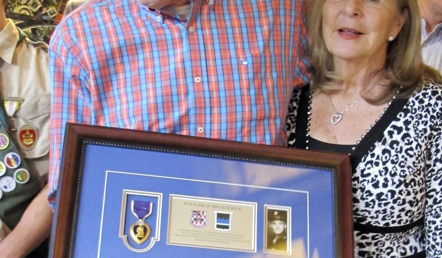 Art Broaderick, with his wife Caryl, holds the framed Purple Heart medal awarded to his father during World War II seven months before he was born during a ceremony on Friday, Dec. 8, 2017, in Burlington, Vt. The medal was returned to Broaderick by the group Purple Hearts Reunited, an organization that reunites medals with the people who won them or their families. Broaderick, of St. Petersburg, who summers in Vermont, was contacted this week by the group's founder Zachariah Fike after the medal was discovered in a Florida thrift store. (AP Photo/Wilson Ring)